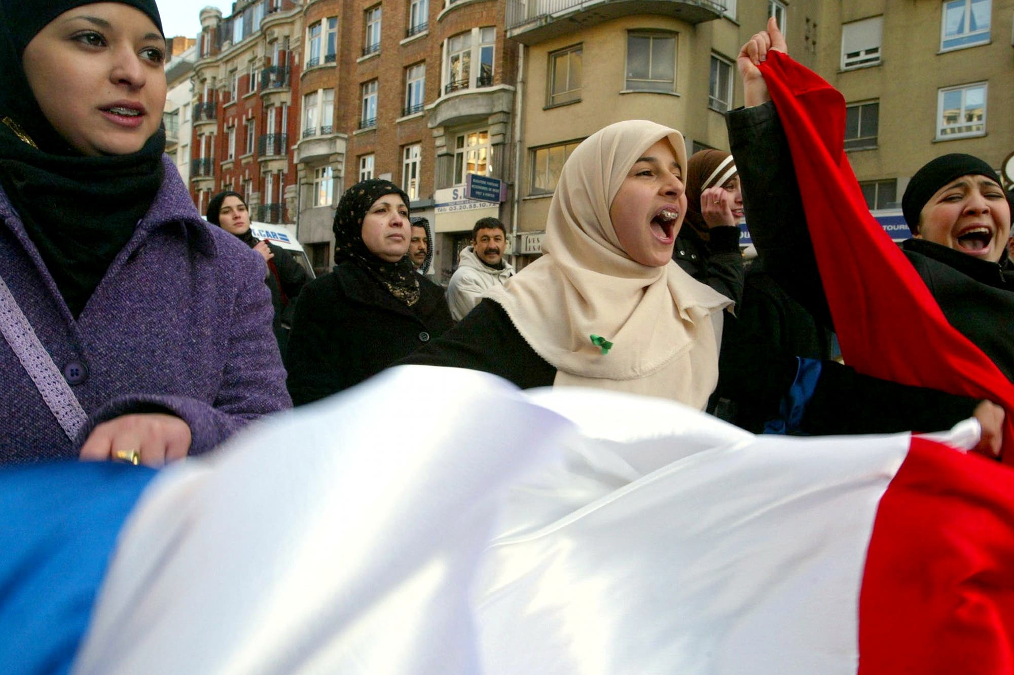 YOUNGS MUSLIMS HOLDING FRENCH FLAG  AND WEARING HEADSCARFS PROTEST IN THE STREETS OF LILLE
