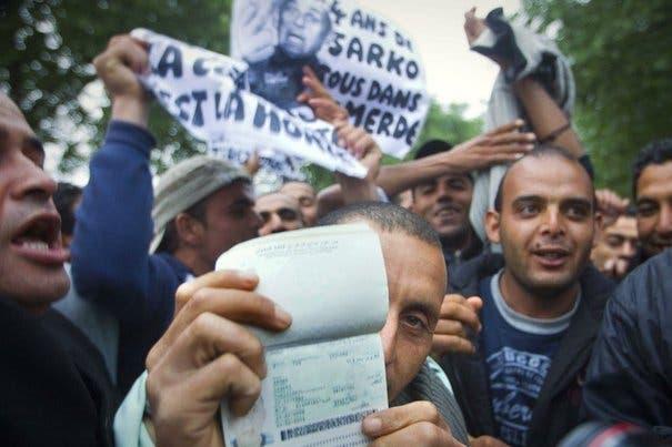 des-tunisiens-montrent-leur-passeport-le-28-avril-a-paris-lors-d-une-manifestation-contre-la-politique-francaise-a-l-egard-des-immigres