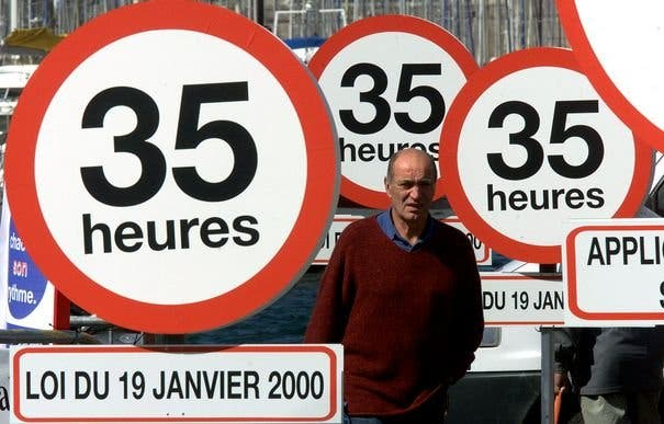 A MAN WALKS PAST SIGN POSTS READING 35 HOURS DURING DEMONSTRATION IN MARSEILLE.