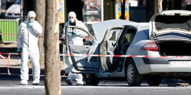 Members of the scientific police inspect a burned car at the scene of an incident in which it rammed a gendarmerie van on the Champs-Elysees Avenue in Paris