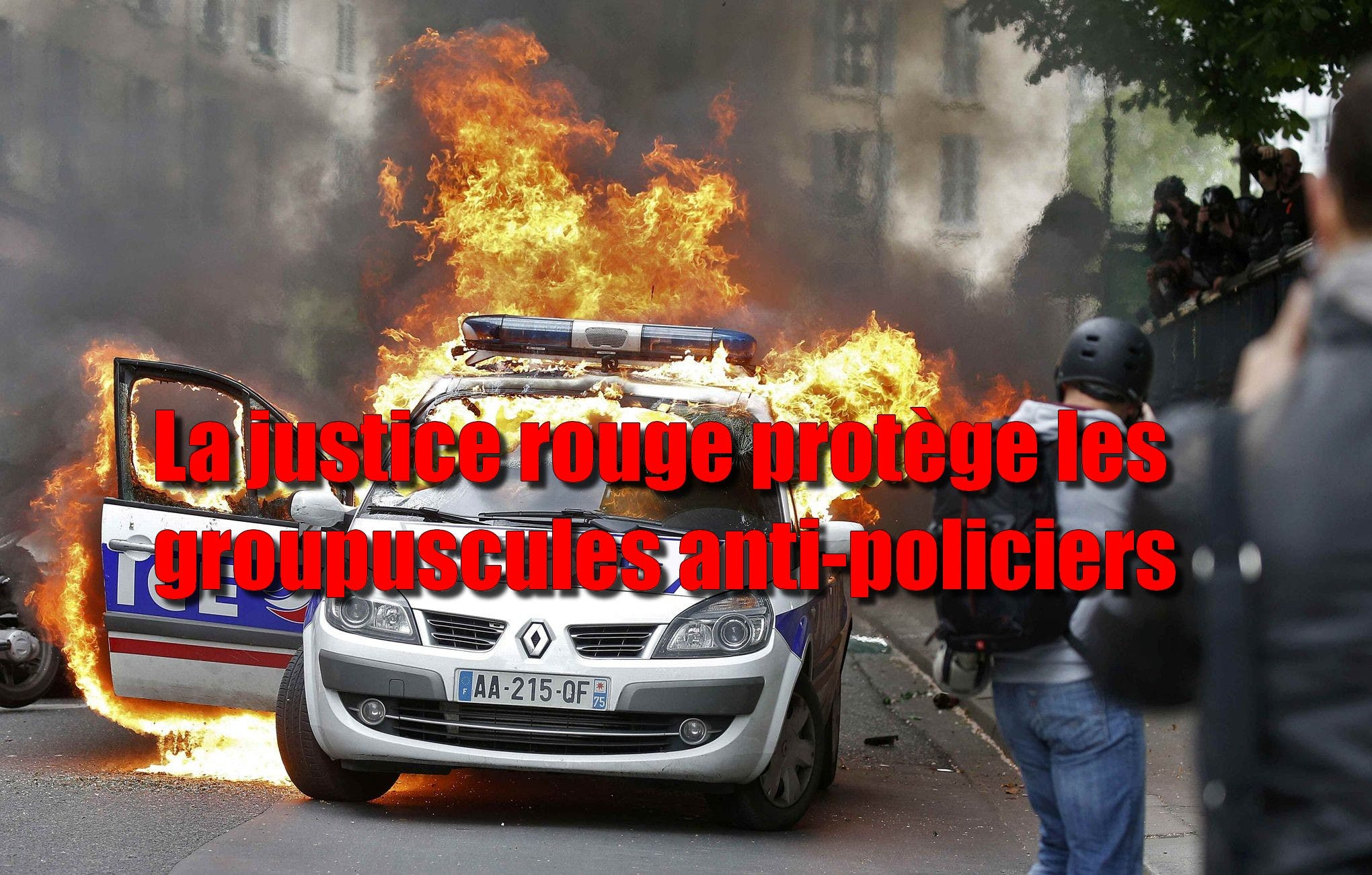 A police car burns during a demonstration against police violence and against French labour law reform in Paris